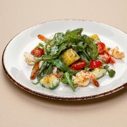 Салат с креветками и овощами под соусом песто на подушке из рукколы